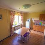 Светлая кухня коттеджа для двух семей. На кухне широкий стол, большой окно, холодильник. База отдыха Розовая дача