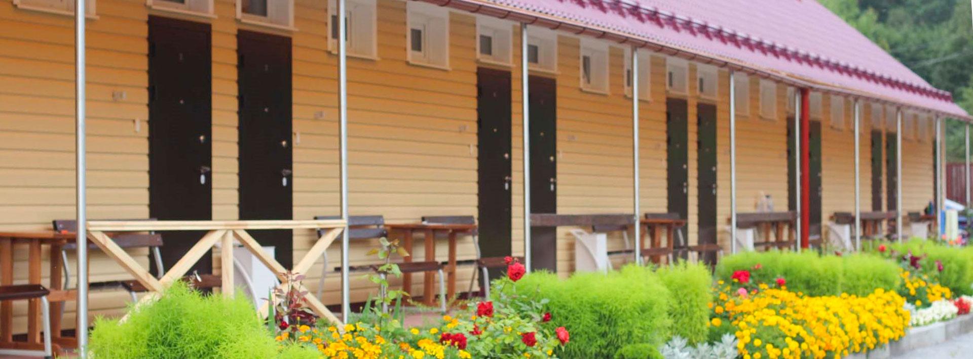 Номера-студио с отдельными входами, столом и лавкой у двери, красивыми газонами. База отдыха Розовая дача